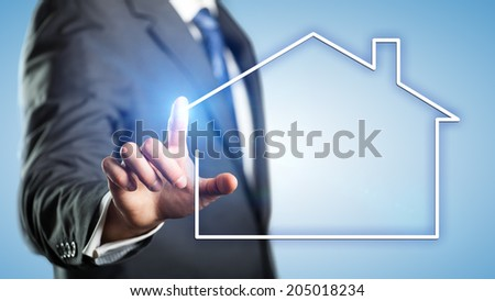 businessman touching an icon of a house
