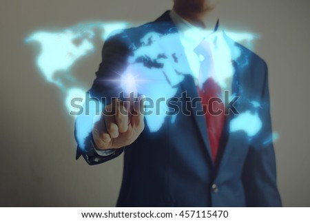 Businessman touching blue virtual world map on screen with blinking light - stock photo