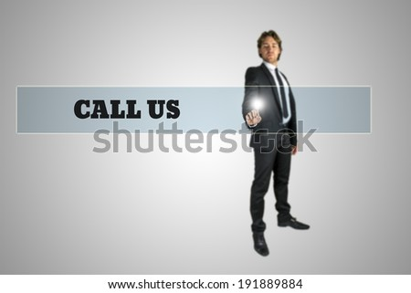 Businessman touching - Call us - navigation bar on a virtual screen with his finger from behind in a conceptual image.  - stock photo