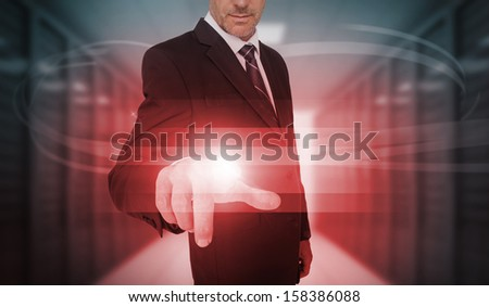 Businessman touching futuristic red light touchscreen in data center - stock photo