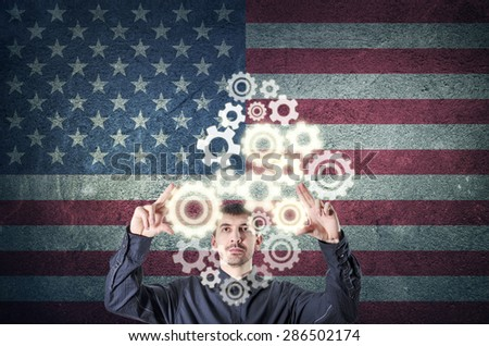 Businessman touching gear elements with USA flag background. Corporate business concept. - stock photo