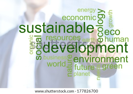 Businessman touching green tag cloud about sustainable development with office buildings in background - stock photo