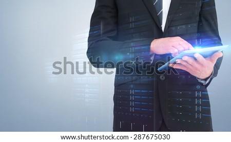 Businessman touching his tablet pc against grey vignette - stock photo