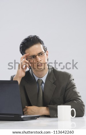 Businessman touching his temple and thinking - stock photo