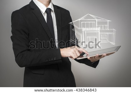Businessman touching screen a model of the house on tablet