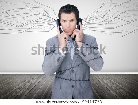 Businessman trapped by telephone wires looking at camera in empty room