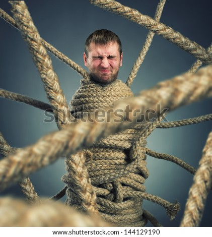 Businessman trapped in rope web - stock photo