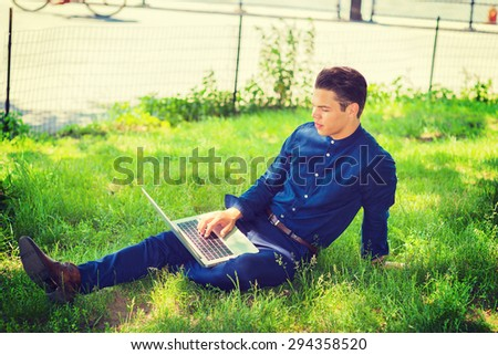 Businessman traveling, working in New York. Wearing blue collarless shirt, a college student sitting on green grasses on campus, reading, thinking, working on laptop computer. Instagram effect. - stock photo