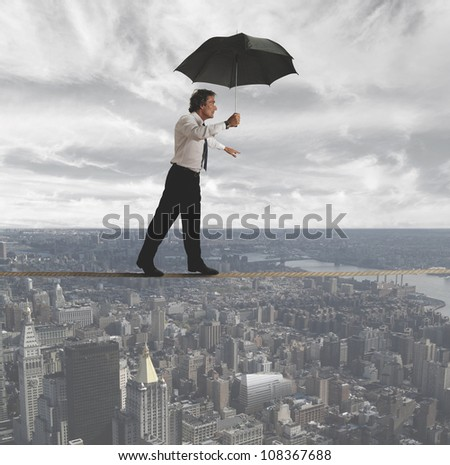 Businessman trying to keep balance between the difficulties - stock photo