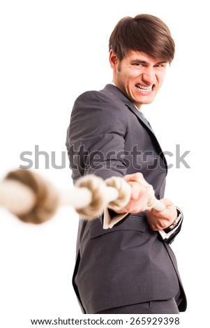 businessman trying to win tug of war - stock photo