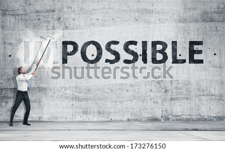 """Businessman turning the word """"Impossible"""" into """"Possible"""" - stock photo"""