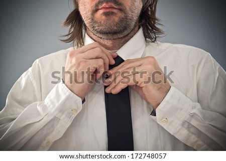 Businessman tying necktie. Man correcting tie, close up with selective focus.