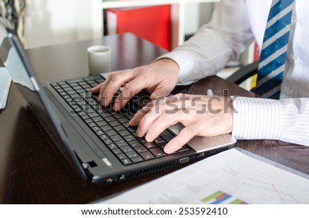 Businessman typing on a laptop at office
