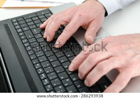 Businessman typing on his laptop, closeup