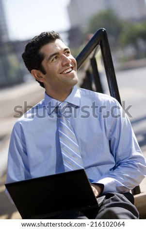 Businessman typing on laptop outdoors