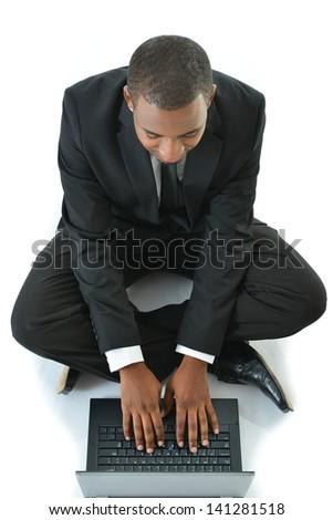 Businessman typing on laptop sitting on floor - stock photo