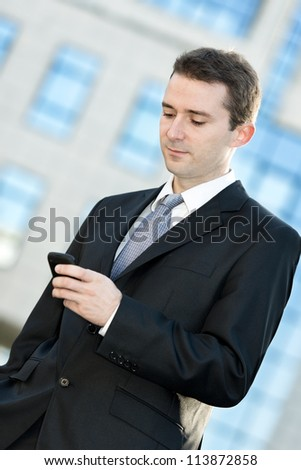Businessman typing on the cell phone - stock photo