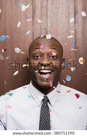 Businessman under falling confetti - stock photo