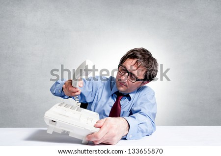 Businessman under stress breaks the handset of the phone - stock photo