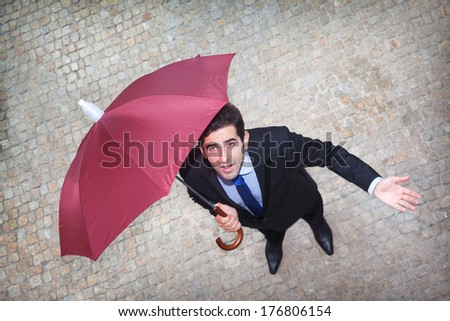 Businessman under umbrella looking worried to the sky and checking if it's raining - stock photo
