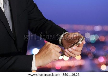 businessman use and touch screen smart phone, cellphone on abstract blurred bokeh of street night light background