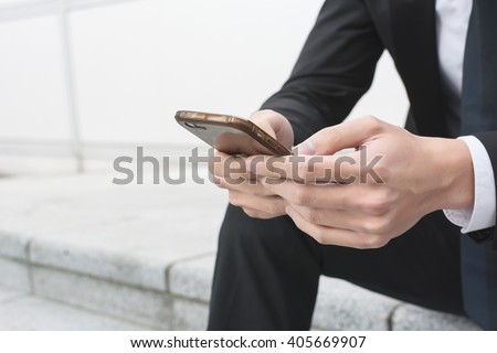 Businessman use of mobile phone and sitting outside
