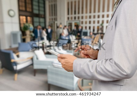 Businessman Use Wireless Tablet Device in Party at Restaurant with Bokeh, Close up shot.