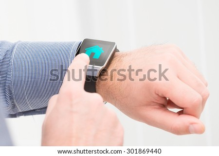 Businessman uses smart watch to home control. Smartwatch concept. - stock photo