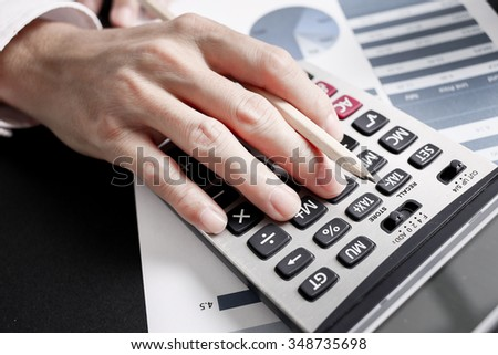 Businessman using a calculator to calculate the numbers. Accounting