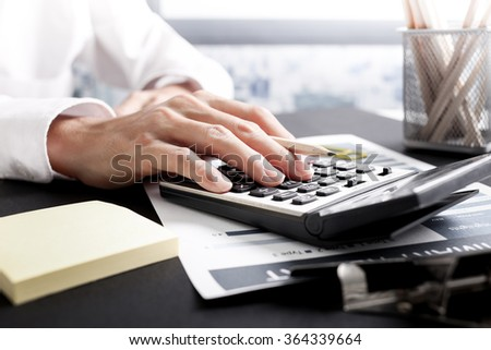 Businessman using a calculator to calculate the numbers. Accounting - stock photo