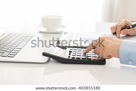 Businessman using a calculator to calculate the numbers. Accounting , Accountancy, Calculation Concept. - stock photo