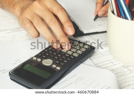 Businessman using a calculator to calculate the numbers. Accounting, soft focus.