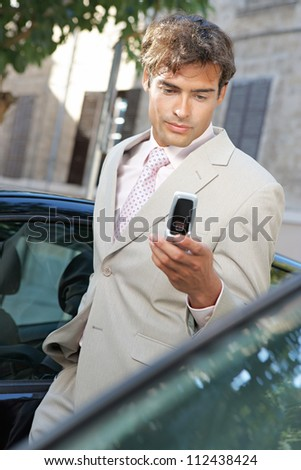 Businessman using a cell phone to send a message while standing by some cars in the city. - stock photo