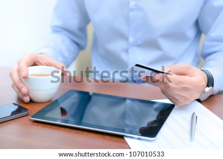 Businessman using a credit card and digital tablet for buying on-line.