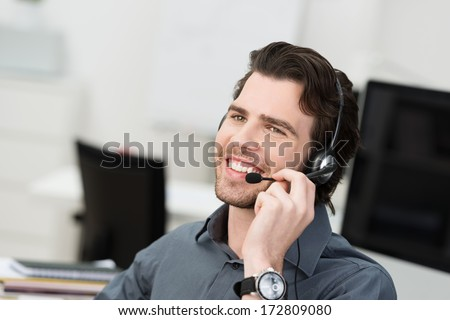 Businessman using a headset for hands free communication or a young call centre operator taking a call at the help desk - stock photo