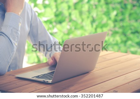Businessman using a laptop, green background