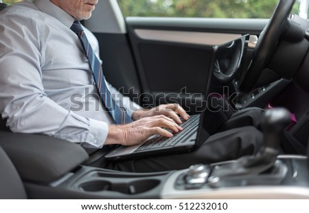 Businessman using a laptop in his car