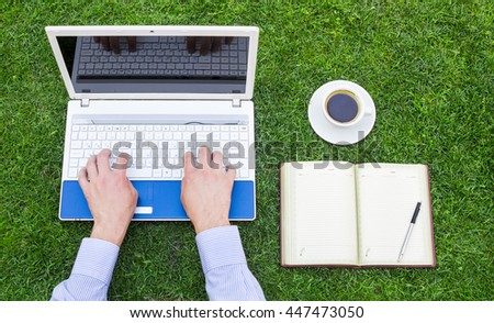 Businessman using a laptop on the grass outdoors; green business and technology concept. - stock photo