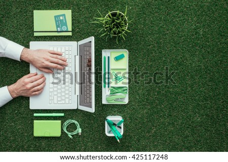 Businessman using a laptop on the grass outdoors; green business and technology concept, top view - stock photo