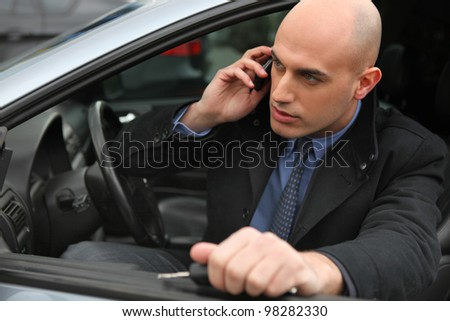 Businessman using a phone in his car - stock photo