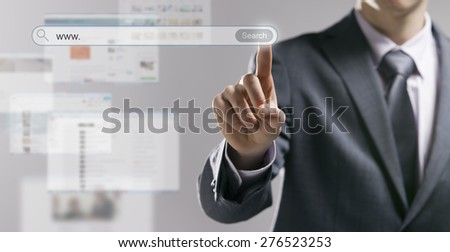 Businessman using a search engine and pressing a search button with web pages on background