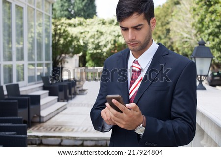 Businessman using a smart phone on the street - stock photo