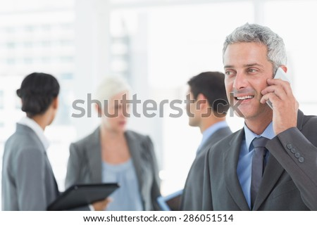 Businessman using a smartphone with colleagues behind in office - stock photo