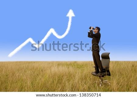 Businessman using binoculars looking growth graph cloud under blue sky - stock photo
