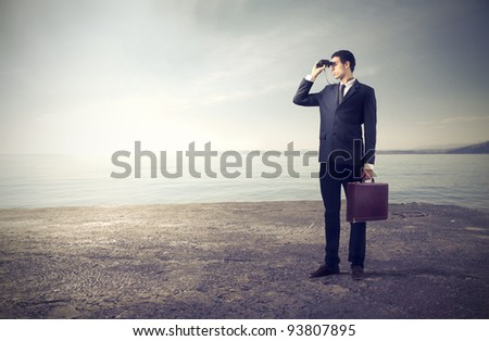 Businessman using binoculars with seascape in the background