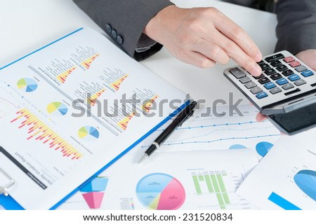 Businessman using calculator analyze report - stock photo