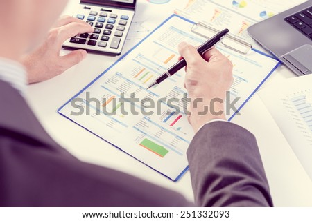 Businessman using calculator analyze report