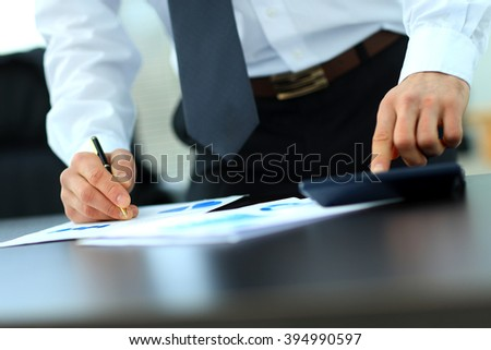 Businessman Using Calculator In Office