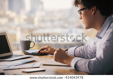 Businessman using calculator on wooden office desktop with laptop, coffee cup, smartphone and business reports. Blurry city background - stock photo