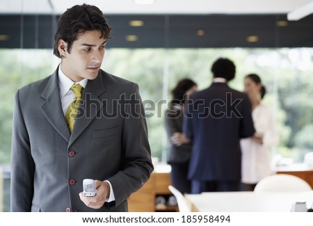 Businessman using cell phone in boardroom - stock photo